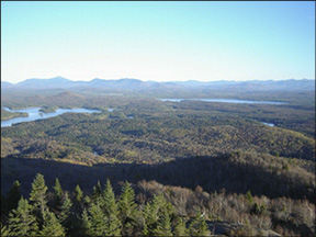 St. Regis Tower Cab View on 21 October 2001, looking south. In the center of this photo is Lake Clear Lake with Upper St. Regis Lake to the left. On the horizon are the High Peaks with Whiteface Mountain visible to the left. Photo courtesty of Friends of the St. Regis Fire Tower.